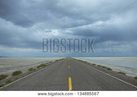Lonely road one point perspective highway yellow stripes against blue gray storm horizon travel trip