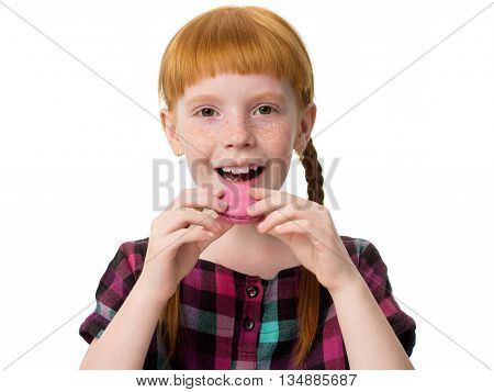 Little redheaded girl with freckles opened her mouth and wants to eat macaron pink cake. Close-up isolated on white background.