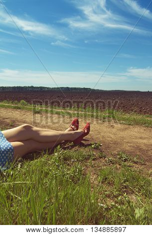 vertical picture of a woman legs with dotted dress and red high heels on a country side road