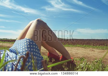 horizontal picture of a woman legs with dotted dress and red high heels on a country side road