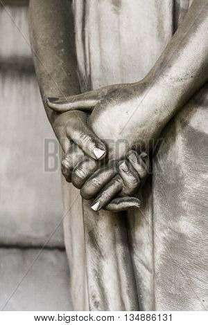 Hands statue of a grieving woman in the monumental cemetery of Staglieno in Genoa.
