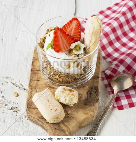 Healthy breakfast. Home crunchy granola with strawberries and cookies Savoiardi portions served in glass cups low. selective focus