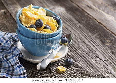 Healthy breakfast. Blue portioned ceramic bowls with corn flakes with fresh blueberries on a dark wooden background with blue creamer on a checkered napkin. selective focus