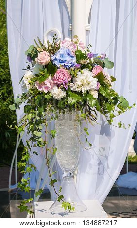 Beautiful bouquet of roses and hydrangeas in a vase on a light background