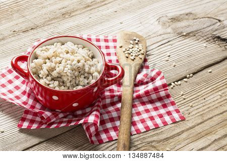 The red ceramic saucepan with white polka dots complete crumbly barley porridge on a simple wooden background with a red cloth in a white cage with a wooden spoon full of dry grain of pearl barley. selective focus