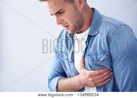 Currently ill. Pleasant sick handsome man holding his hand on the heart and feeling pain while standing isolated on white background