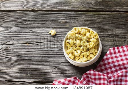 White ceramic bowl full of Italian pasta tortellini to cooking on a dark wooden background with structural tissue in a red white checkered.
