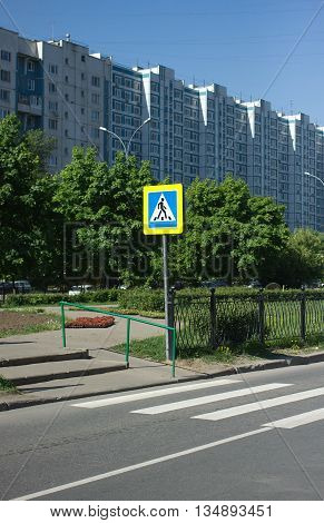Pedestrian crossing sign on city street in front of striped road marking in summer day, vertical photo