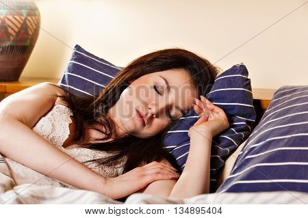 Young Woman Sleeping On The White Bed-clothes In Bed