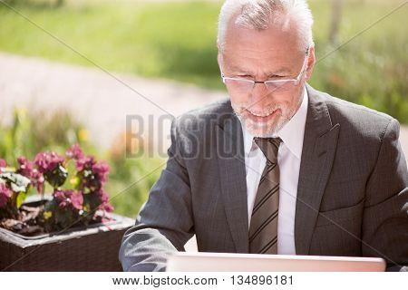 Full of gladness. Positive smiling senior businessman sitting at the table and using laptop while expressing joy