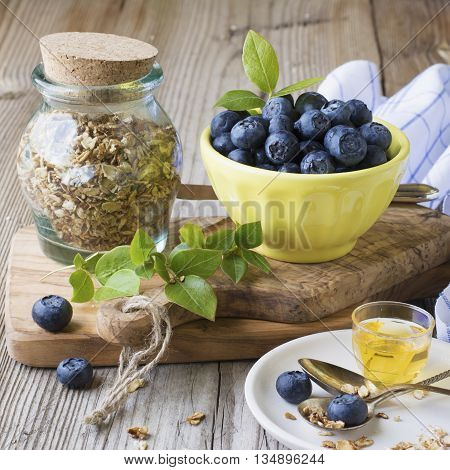 Still life of healthy breakfast. Cereal flakes for cereal, blueberry ripe berries, fresh flower honey, nuts on a cutting board from olive wood are served with table linens in a cage. selective focus