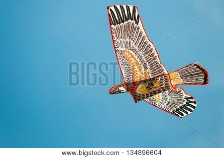 Bird shaped kite flying in blue sky. Concept of freedom