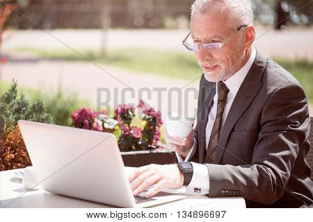 Refresh your mind. Pleasant content senior businessman sitting at the table and drinking coffee while using laptop