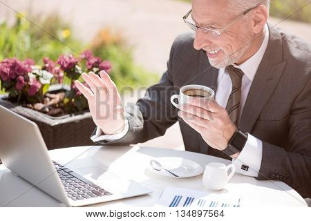 Pleasant talk. Positive smiling senior man sitting at the table and drinking coffee while talking through the Internet