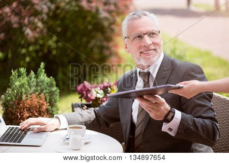 Here you are. Cheerful senior smiling man sitting at the table and holding folder while looking aside