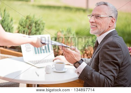 Thank you. Positive handsome senior man sitting at the table and holding folder while expressing gladness