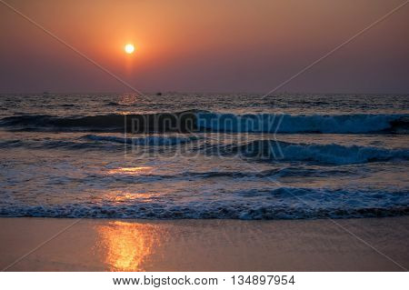 Beautiful red sunset over Goan beach with reflections and ocean waves
