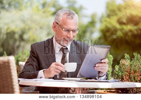 Modern user. Positive smiling senior man sitting at the table and using tablet while drinking coffee