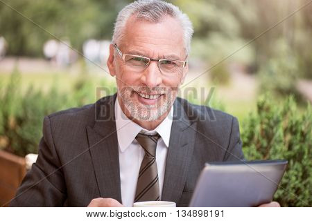 Stay positive. Portrait of smiling cheerful senior man sitting at the table and drinking coffee while expressing joy