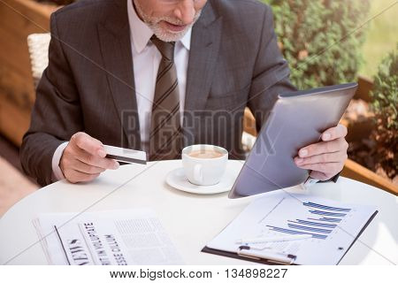 Money maker. Pleasant concentrated senior man sitting at the table and holding credit card while using tablet