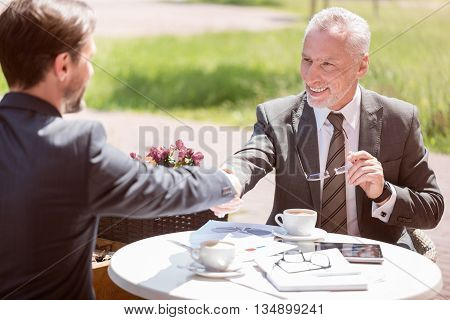 Find right decision. Pleasant cheerful smiling colleagues sitting at the table and shaking hands while expressing gladness