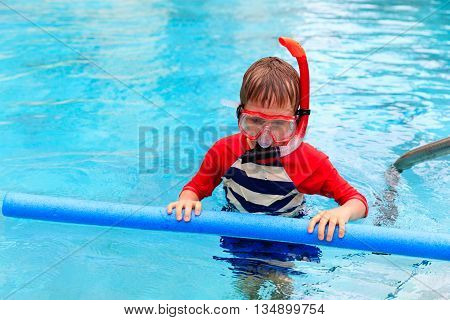Little boy learns swimming alone with pool noodle, kids sport