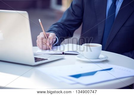 Working atmosphere. Pleasant man sitting at the table and making notes while using laptop