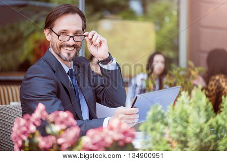 Optimistic vision. Pleasant cheerful smiling man sitting at the table and using tablet while having relaxation in the cafe
