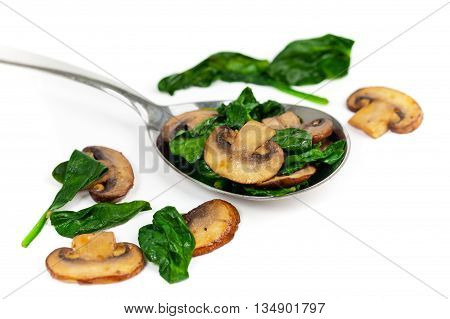 Sauteed Mushrooms and Spinach on White. Selective focus.