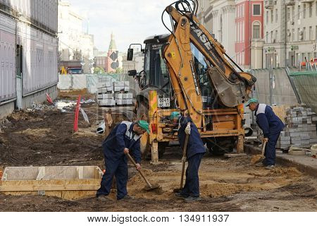 MOSCOW, RUSSIA - MAY 15, 2016: Building machinery and workers with shovels. Reconstruction of the roadway within the city beautification program My Street in Moscow.