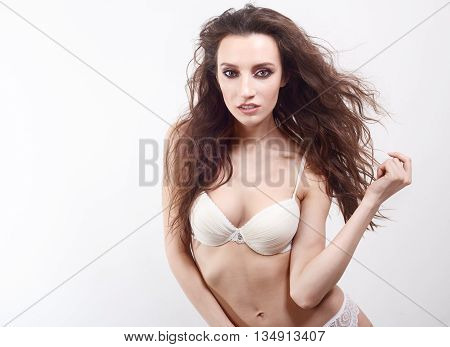 Alluring woman in underwear posing, on white background. Model with brunette, flying hairs.