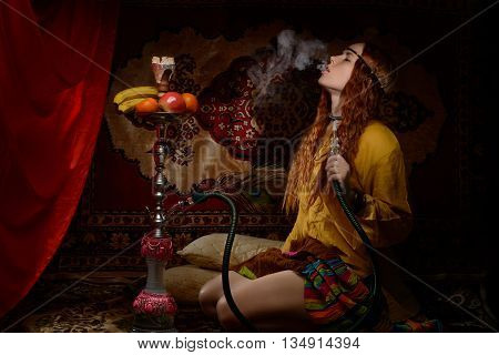 Young woman dressed in hippie style smoking hookah