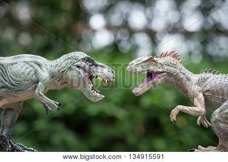 tyrannosaurus and allosaurus toy in front of trees