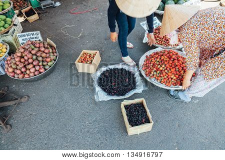 NHA TRANG VIETNAM - JANUARY 20: Woman is selling strawberry and mulberry at the wet market on January 20 2016 in Nha Trang Vietnam.