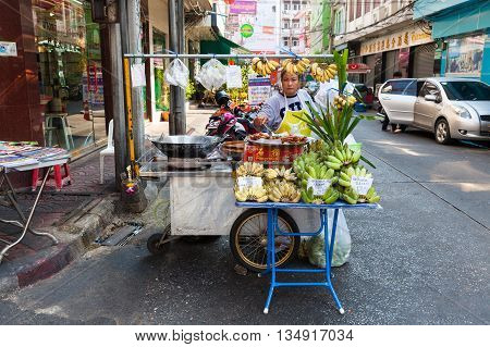 BANGKOK THAILAND - APRIL 24: Woman selling fruits on the street of Bangkok Chinatown on April 24 2016 in Bangkok Thailand.