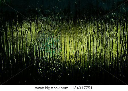 The light through the dark green glass with abstract pattern
