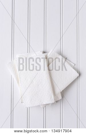 High angle view of a pile of white paper napkins on a white picnic table. Vertical format with copy space.