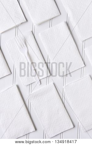 White Napkins on a White Table. A single plastic fork on one napkin. Vertical format from a high angle.