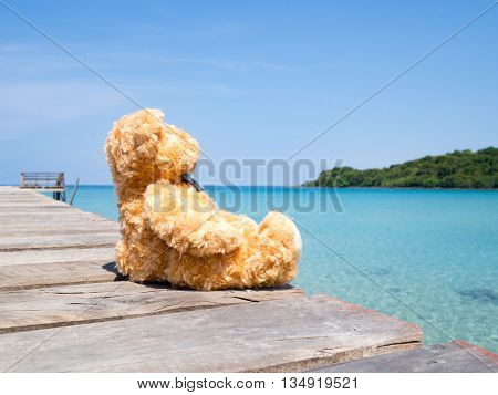 Brown cute bear doll sitting alone on wooden pier looking at sea view. Concept of loneliness.