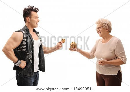 Punk rocker taking cookies from a senior lady isolated on white background