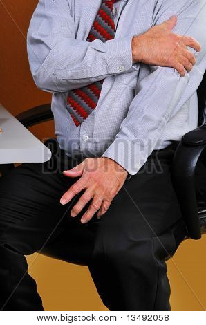 Businessman feeling pain in his arm