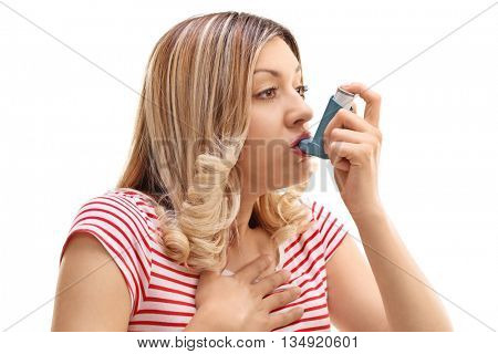 Young woman inhaling her asthma medication isolated on white background