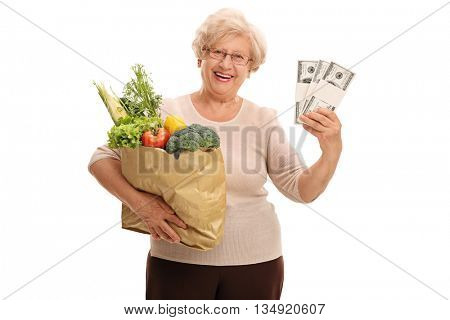 Mature lady holding a bag of groceries and a few stacks of money isolated on white background
