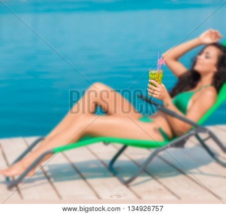 Attractive brunette on the beach. Young woman in swimwear drinking coctail on the beach