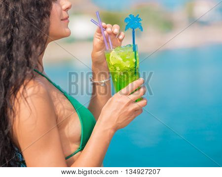 Young woman in swimwear drinking coctail on the beach