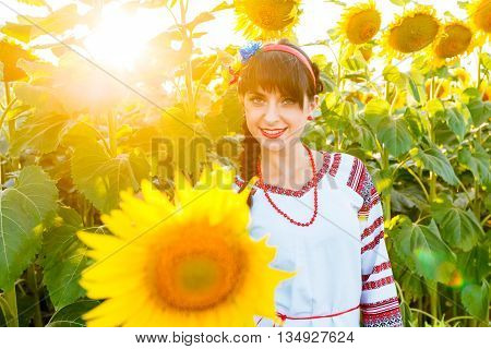 Beautiful young girl in national ukrainian blouse embrodery looking to camera on a sunflower plant at sunset backlight.