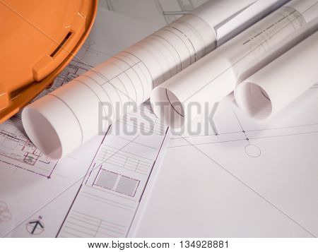 Architect rolls and plans technical project drawing on table (Selective focus)