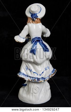 porcelain figurine in the form of a girl in medieval dress isolated on a black background