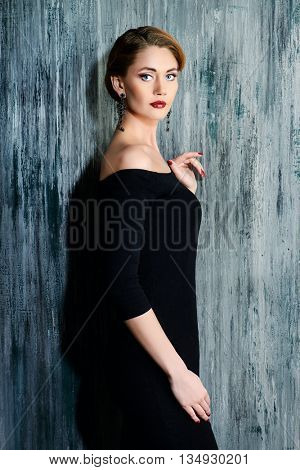 Charming young woman wearing black fitting dress. Jewellery. Fashion shot.