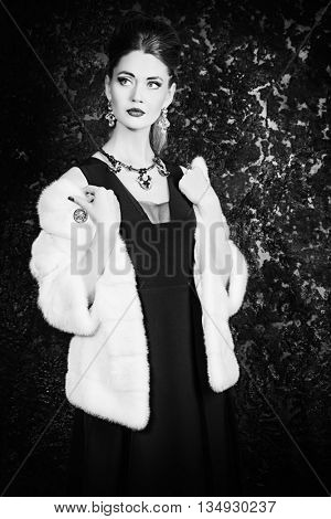 Black-and-white portrait of a beautiful young woman wearing mink fur jacket. Jewellery. Beauty, fashion. Studio shot.